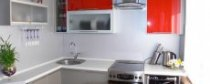 Малогабаритна світла кухня з червоним кухонним гарнітуром, плитою, духовкою, витяжкою, краном, мийкою і стільницею.  Маленька кухня 6 кв.  м. в квартирі або будинку.